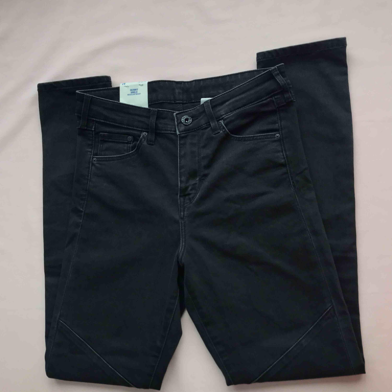 💌Frakt ingår!💌 Stretchiga skinny jeans i mörkgrått från H&M med detaljer framtill och dragkedja längst ned • storlek 28, aldrig använda!. Jeans & Byxor.