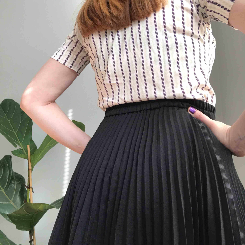 Så tjusig, knälång, plisserad kjol i svart • ingen lapp men kjolen passar storlek S-L pga stretchigt resårband i midjan • väldigt fint skick ☁️Frakt tillkommer☁️. Kjolar.
