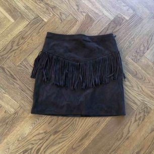 Kort mörkbrun kjol i mocka-imitation. Fransar framtill. Haft den i många år men har nästan aldrig använt den så den är i mycket gott skick!