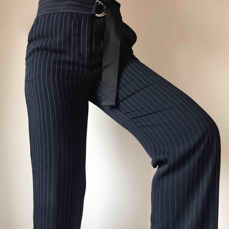 Utsvängda mörkblåa kritstrecksrandiga kostymbyxor i mjukt härligt material från Mango • stängs med dragkedja, knapp och inbyggt skärp • storlek 38 men passar 40/42 bättre • sömmen längst ned på ena benet har släppt, se bild ☁️Frakt tillkommer☁️. Jeans & Byxor.