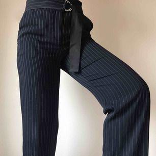 Utsvängda mörkblåa kritstrecksrandiga kostymbyxor i mjukt härligt material från Mango • stängs med dragkedja, knapp och inbyggt skärp • storlek 38 men passar 40/42 bättre • sömmen längst ned på ena benet har släppt, se bild ☁️Frakt tillkommer☁️