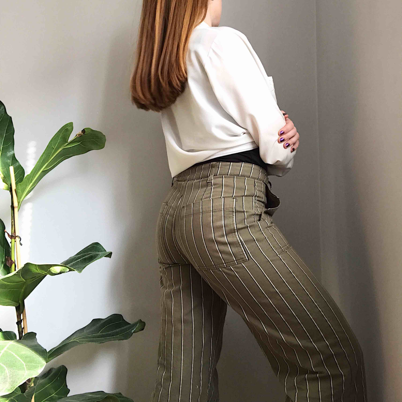 Randiga khakigröna byxor från Urban Outfitters • köpta förra sommaren och använda ett fåtal gånger • storlek S men skulle sitta bättre på en medium eller en liten large ☁️Frakt tillkommer☁️. Jeans & Byxor.