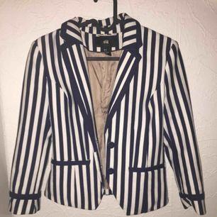En blå, vit randig kavaj jacka från H&m. Med fake fickor och två knappar så att den går att stänga. Den är lite liten i storleken så den sitter typ som en 34. Aldrig använd. Köparen står för frakten. Vid snabb ät köp så kan frakten ingå i priset.🙂