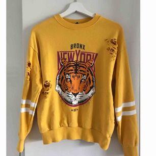 Gul tröja med tiger och slitningar i storleken XS. Använd 3-4 ggr, väldigt bra skick, som ny.