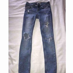 Blåa slitna jeans från Gina i modellen KRISTEN i storleken 25, lågmidjade.