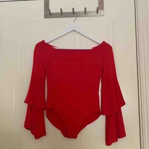 Röd långärmad off shoulder body med volang i ärmarna. Köpt från Boohoo i storlek 32. Frakt ingår.