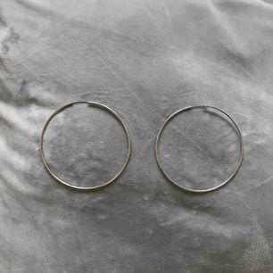 Stora hoops, silverfärgade örhängen. 10cm i diameter. Köpta på Glitter, aldrig använda