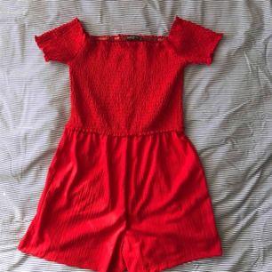 Jättefin röd off shoulder jumpsuit från Bershka strl M, resorband som håller den uppe vid axlarna. Aldrig använd.