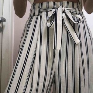 """Superfina kostymbyxor från Zara """"collection"""" i benvit färg. Ränderna är mörkblå samt supertunna silverränder. Jag är 160 cm långoch byxorna går till ankeln på mig. Byxorna har ett knytband i midjan. Jag står för frakt!"""