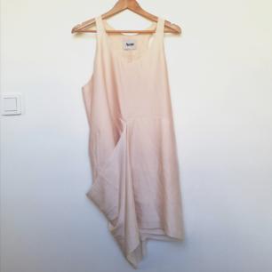 Asymmetrisk draperad klänning från Acne Studios i stl 38. Så fin och ovanlig på. Gjord i ett siden-likande material som känns lyxigt och flowy. Ljust puderrosa och perfekt för studenten eller skolavslutningen nu när det börjar bli dags. Går ner till knäna ungefär där draperingen är som längst, resten är lite kortare. Modellen heter Magenta Tank Dress i färgen