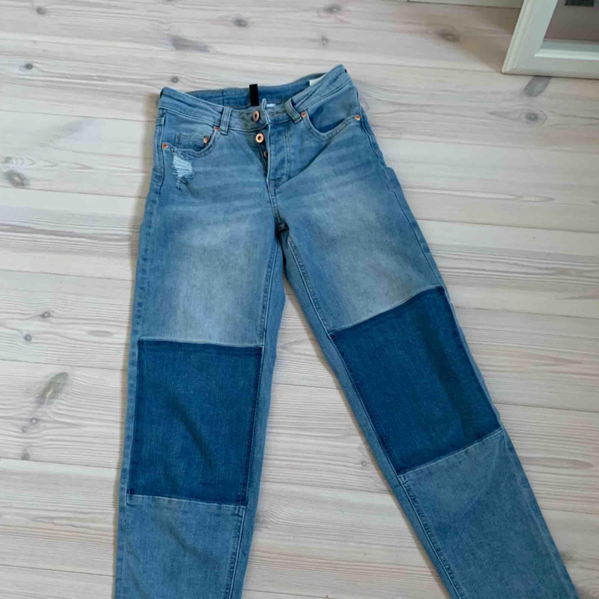 Jeans som är ihoplappade med olika färger på jeansen. Vid ankeln är byxbenet asymmetriskt och slitage på fram och bakfickan. Nästan aldrig använda. Jeans & Byxor.