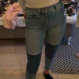 Jeans som är ihoplappade med olika färger på jeansen. Vid ankeln är byxbenet asymmetriskt och slitage på fram och bakfickan. Nästan aldrig använda