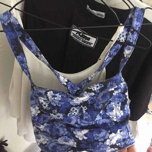 Jättesöt blå, blommig topp. Passar jättebra nu till sommaren! Korsade band i ryggen. Fraktar