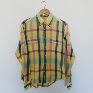 Somrig färgglad rutig skjorta på gul botten från Gant Rugger i stl M herr. Gjord i 100% bomull. I bra skick förutom ett minimalt hål på vänstra bröstet, går nog att laga lätt! Två bröstfickor och buttondown-krage. Frakt 59 kr.