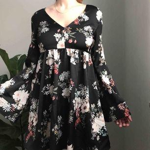 Fantastisk blank v-ringad klänning i svart med blommönster från Mango • inbyggda shorts under klänningen och vida ärmar • klänningen är lite tyngre vilket ger en lyxig känsla 💌Frakt tillkommer med 54kr💌