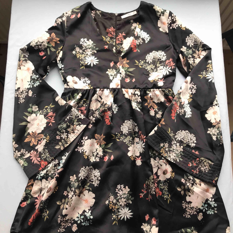 Fantastisk blank v-ringad klänning i svart med blommönster från Mango • inbyggda shorts under klänningen och vida ärmar • klänningen är lite tyngre vilket ger en lyxig känsla 💌Frakt tillkommer med 54kr💌. Klänningar.