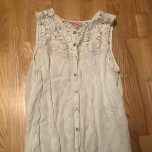 Säljer en fin vitt somrig topp. Den är ett linne och har spets upptill. Den är i storlek 158/164 men passar också XS