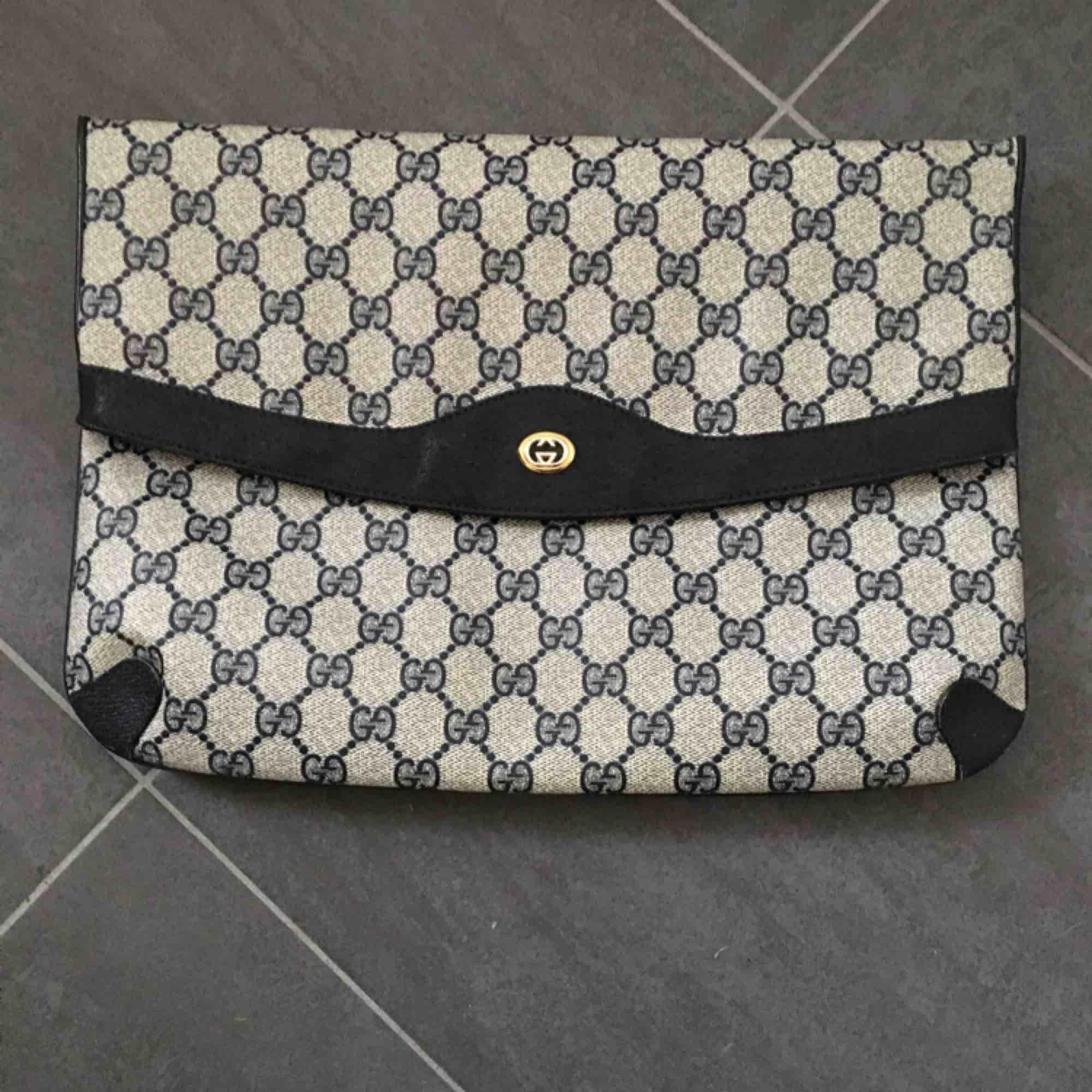 """Jättefin Gucciväska- vintage. Svart med klassiskt Gucci-mönster . På insidan finns en dold ficka med dragkedja. Storleken är 32x23 cm. Finns ett äkthetscertifikat i väskan. På """"fållkanten"""" i läder finns ett litet hack på varje sida (se bild).. Väskor."""