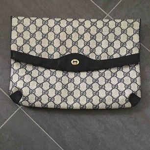 """Jättefin Gucciväska- vintage. Svart med klassiskt Gucci-mönster . På insidan finns en dold ficka med dragkedja. Storleken är 32x23 cm. Finns ett äkthetscertifikat i väskan. På """"fållkanten"""" i läder finns ett litet hack på varje sida (se bild)."""