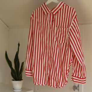 Randig skjorta med slits på sidorna. Skulle säga att den passar en medium också! Använd ett fåtal gånger!