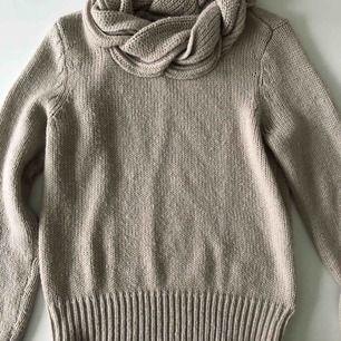 En mysig kabelstickad tröja i en beige färg , använt ett fåtal gånger , bra skick , flätad krage