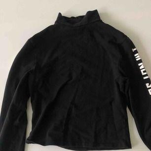 En croppad svart tröja , använt ett fåtal gånger , väldigt bra skick, i båda armarna är det vit text , den har även en halv polo krage
