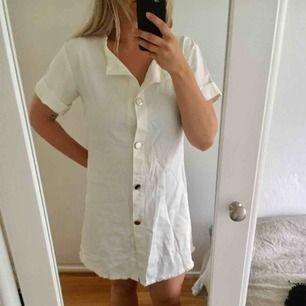 Super fin vit klänning, i bomull (nästan lite jeansliknande material). Perfekt sommarklänning!  I bra skick, men kan behöva en strykning samt att det saknas en knapp längst ner, men går att köra ändå, eller sy dit en ny såklart.   Köpt från Asos.