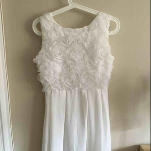 """Vit klänning med """"blommor"""", i mycket fint skick då den endast är använd en gång"""