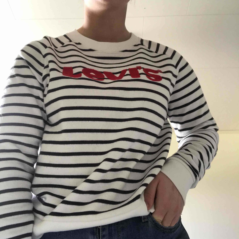 Jättefin randig tröja med broderad text från Levis. Använd men i nyskick. Köpare står för frakt. . Huvtröjor & Träningströjor.