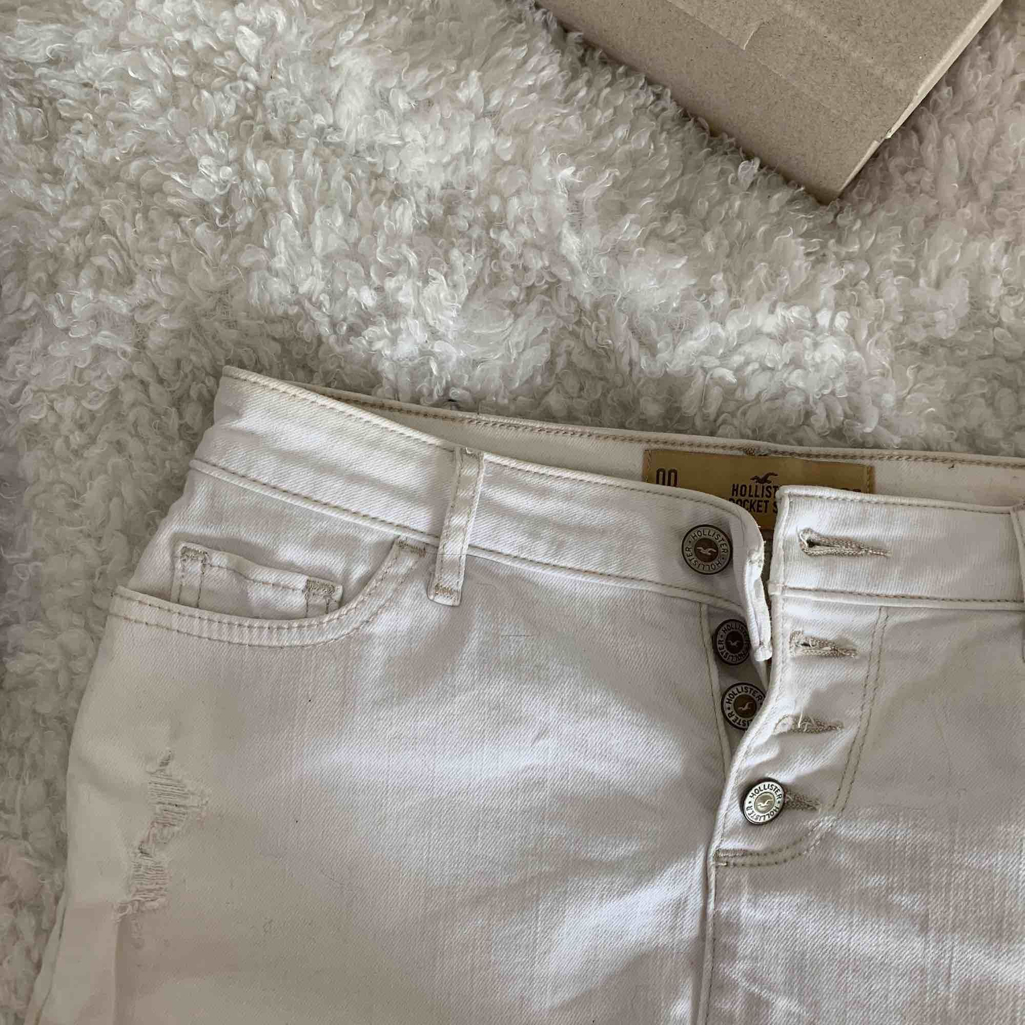 Vit kort kjol från Hollister med slitningar! 🤩 Sitter som en smäck, men används tyvärr inte så mycket av mig! 😖 Frakt ingår!💌. Kjolar.