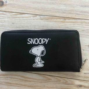 En ganska stor plånbok med ett motiv på Snoopy.