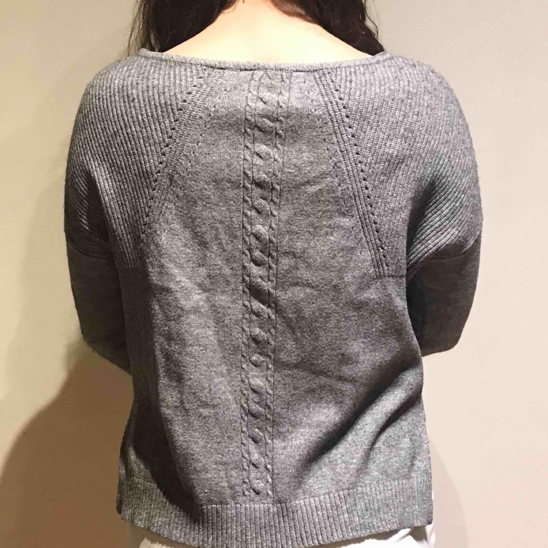 Grå, gullig stickad tröja med jack på vardera sida! . Stickat.