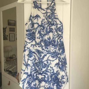 Helt ny jumpsuit (prislapp sitter kvar) från märket Xenia i Australien. Vit/blå med blommigt mönster. Halterneck-modell med öppen rygg. Nypris ca 450 kr. Storlek L/UK 12.