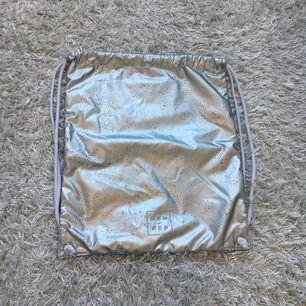 En silvrig träningsväska från H&M. Den är använd men bra skick. Jag kan frakta men då får köparen står för frakten.