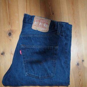 Graue Levis Jeans in den Größen W33 und L38. Kleine Fransen an den Beinen. Die Jeans ist in den Beinen etwas kürzer und leicht weit geschnitten.