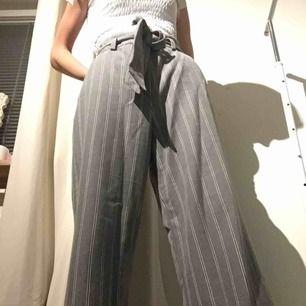 Grå randiga kostym byxor, följer med en extra knap. De passar på storlekar under 38 eftersom man knyter i midjan. Har inte används endast testade, de är som nya. Tar Swish och kan mötas up i Stockholm men postar även, köpare står för frakten. :)