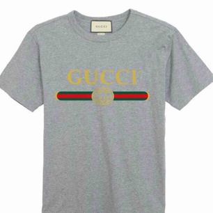 Gucci  Fabric:100 Percent Cotton   Color:Grey    Sleeve:Half Sleeve   Pattern:Printed   Neck Shape:Round   Fit:Regular Fit