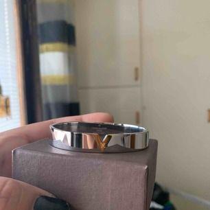 Bangle i guld och vit (stain less steel hypoallergenic) oanvänd..box ingår och frifrakt. 150/st.  Oäkta !!!