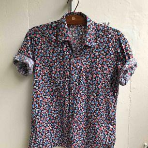 Mycket snygg kortärmad blommig skjorta. Inköpt i London. Tyvärr för liten för mig (bär oftast M).