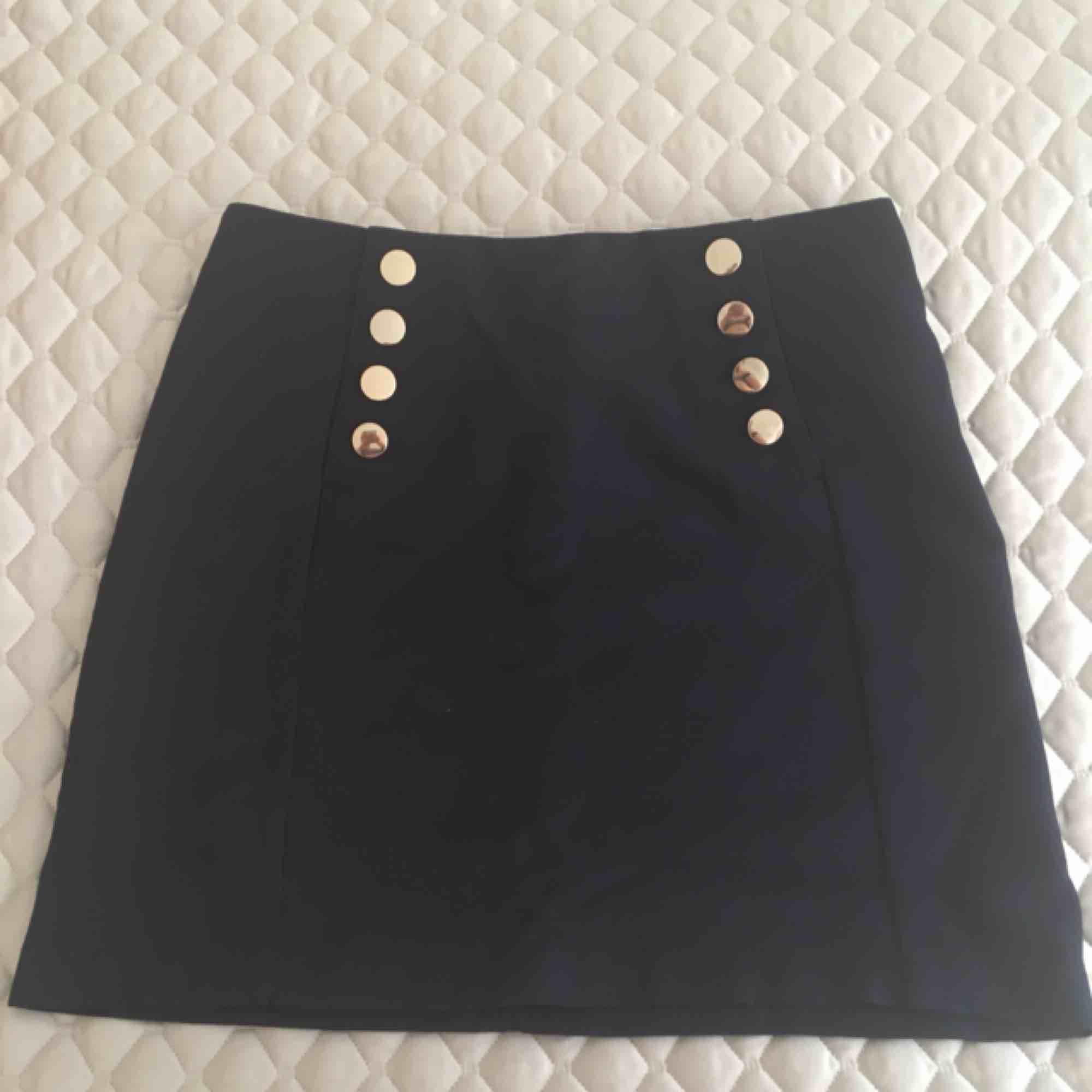 Marinblå kjol i vävd struktur från H&M med guldfärgade knappar framtill. Aldrig använd. Hämtas i Malmö alternativt står köparen för frakt. . Kjolar.