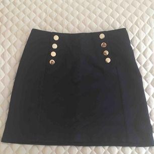 Marinblå kjol i vävd struktur från H&M med guldfärgade knappar framtill. Aldrig använd. Hämtas i Malmö alternativt står köparen för frakt.