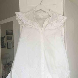 """Söt vit blus med krage och krås/volanger upptill från H&M. Liten """"ärm"""" som går över axlarna. Hämtas i Malmö alternativt står köparen för frakt."""