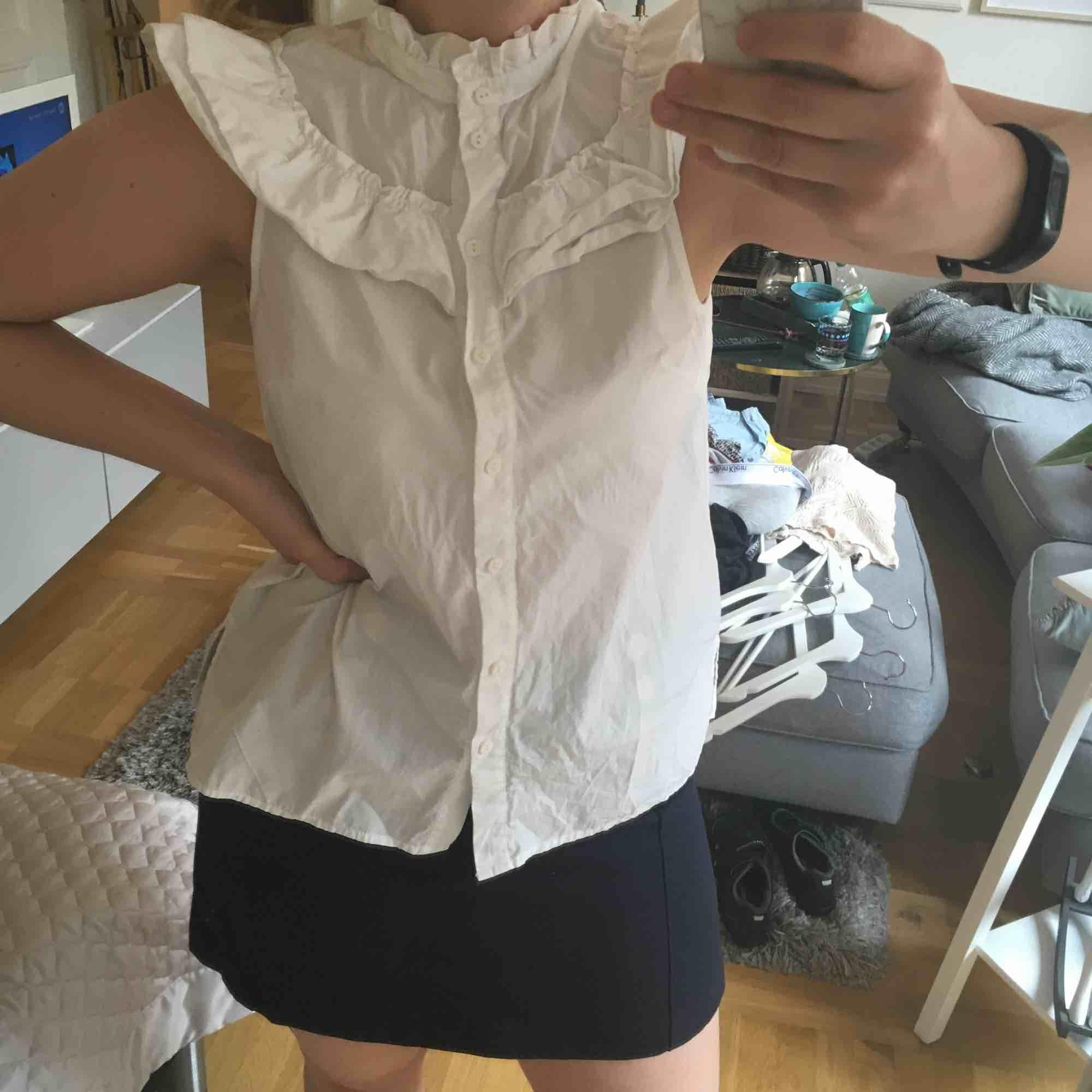 """Söt vit blus med krage och krås/volanger upptill från H&M. Liten """"ärm"""" som går över axlarna. Hämtas i Malmö alternativt står köparen för frakt. . Blusar."""