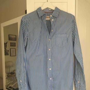 Randig ljusblå/vit skjorta från Holly & Whyte by Lindex. Sparsamt använd. Hämtas i Malmö alternativt står köparen för frakt.