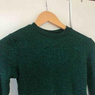 Grön glittrig croptop i storlek S. Är från Urban Outfitters, nypris runt 300 kr. Superfint skick. Köparen står för frakt