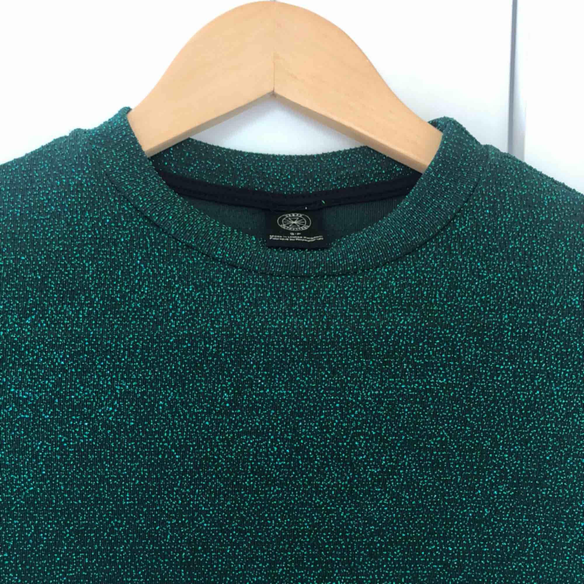 Grön glittrig croptop i storlek S. Är från Urban Outfitters, nypris runt 300 kr. Superfint skick. Köparen står för frakt. Toppar.