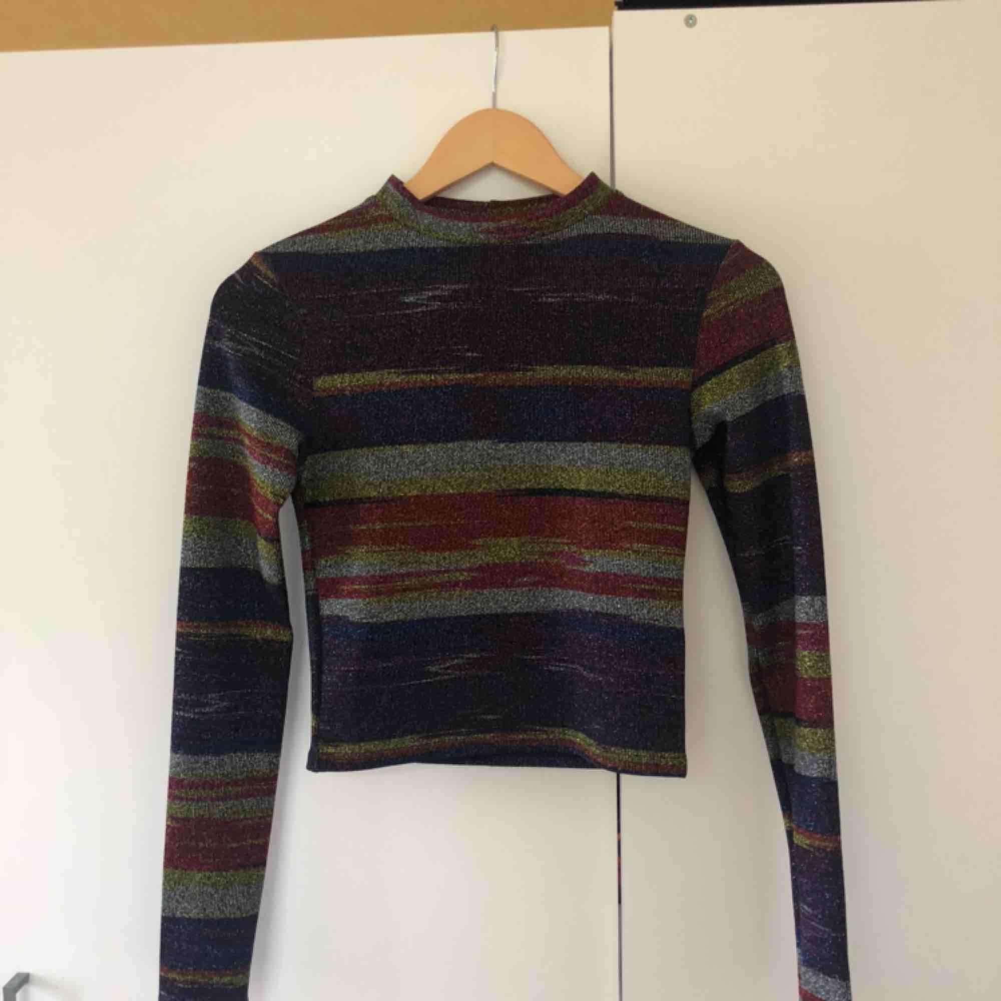 Glittrig långärmad tröja från Urban Outfitters. Jättecoola färger, är i storlek S och nyskick. Köparen står för frakt.. Toppar.
