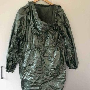 Asball regnjacka från Visual Clothing Project. I metallaktig ljusgrön. Tunn. Går att justera passform. I superbra skick. Storlek S. Köparen står för frakten.