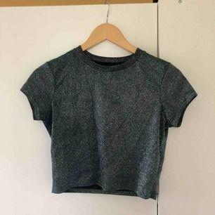 Glittrig t-shirt från Urban Outfitters som skiftar i silver/blå/grön (syns ej på bilderna). I superfint skick, storlek S. Köparen står för frakten