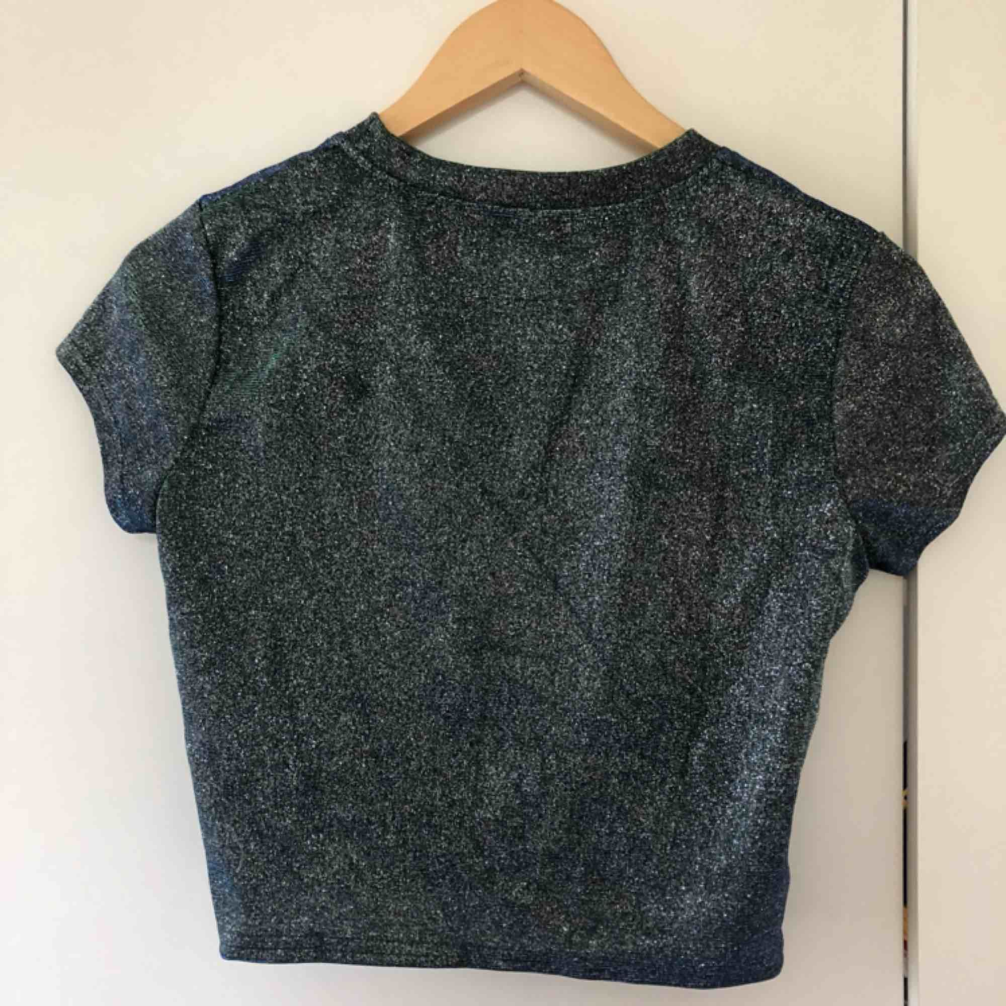 Glittrig t-shirt från Urban Outfitters som skiftar i silver/blå/grön (syns ej på bilderna). I superfint skick, storlek S. Köparen står för frakten. T-shirts.